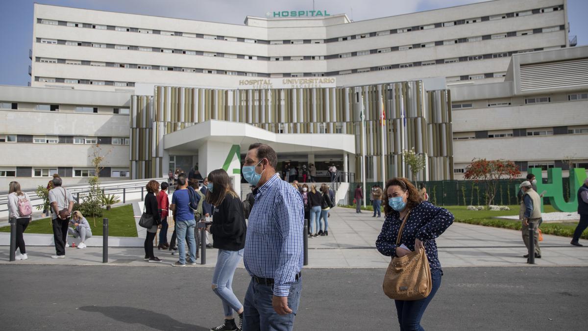 Varias personas caminan alrededor del Hospital Universitario Virgen Macarena de Sevilla.