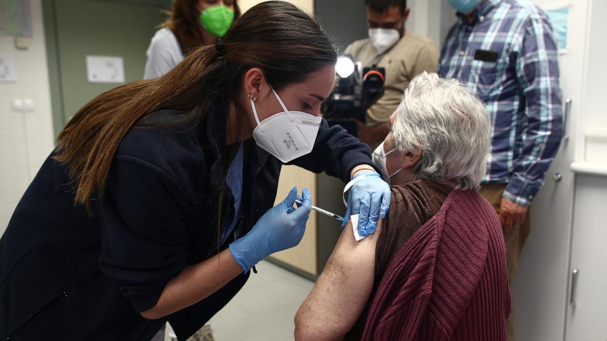 Una sanitaria inyecta una dosis de la vacuna de Pfizer a una anciana.
