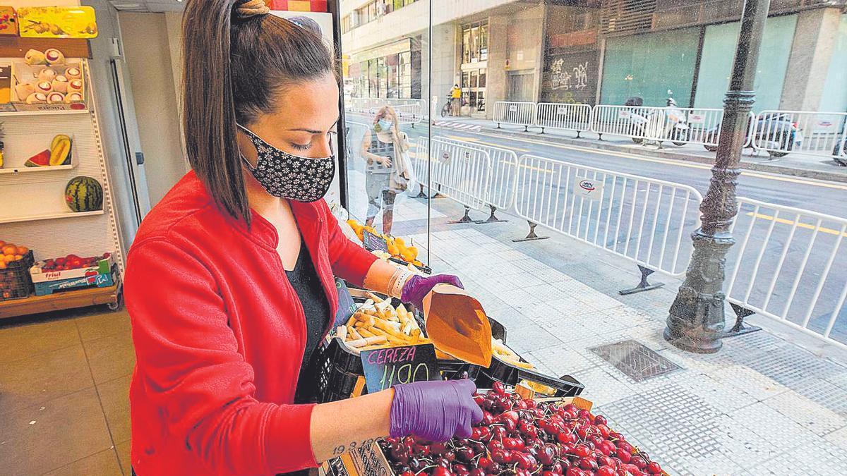 Una frutera recoge unas cerezas en una tienda de la capital aragonesa.