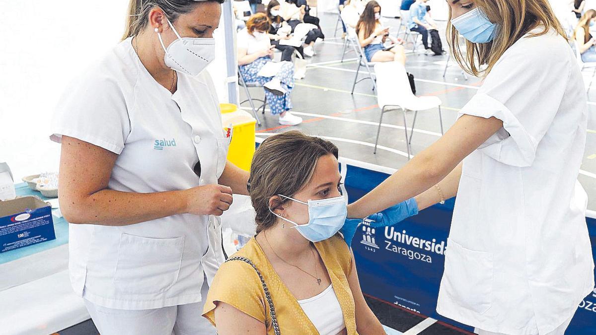 Dos enfermeras vacunan a una joven contra el covid en el pabellón de la Universidad de Zaragoza.