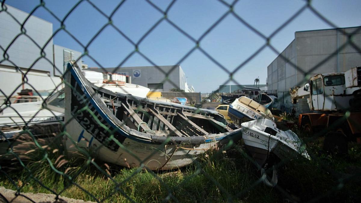 Uno de los cayucos y varias de las lanchas abandonadas en el potrero de la Autoridad Portuaria el pasado viernes.