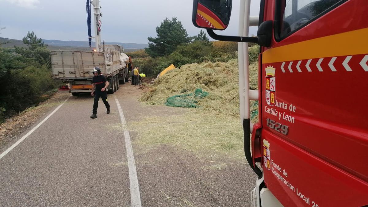Los bomberos retiran parte de la paja de la carretera tras el siniestro.