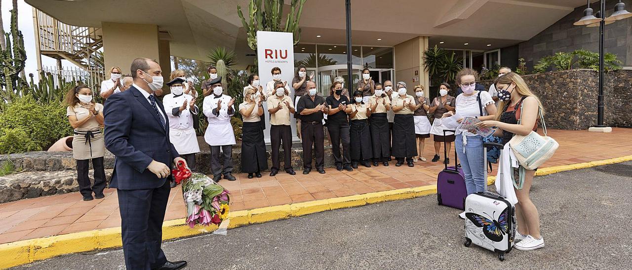 El director del hotel Oliva Beach, José María Vázquez, recibe con un ramo de flores a las dos primeras turistas llegadas al establecimiento tras su reapertura.