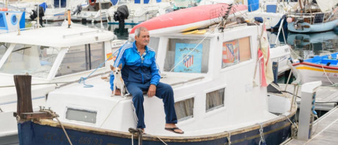 El marinero Benigno Marrero, alias Nino, junto a su perro Thor en su barco del Muelle Deportivo.