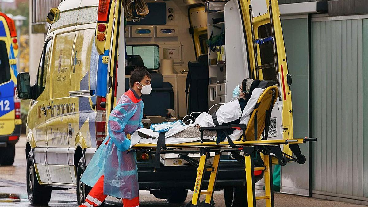 Un paramédico saca a una mujer de una ambulancia frente al Hospital de Burgos.     // AFP/CÉSAR MANSO
