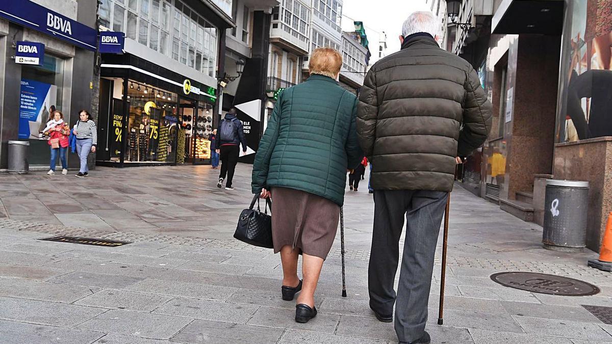 Dos personas caminan por la calle Real de A Coruña.     // VÍCTOR ECHAVE