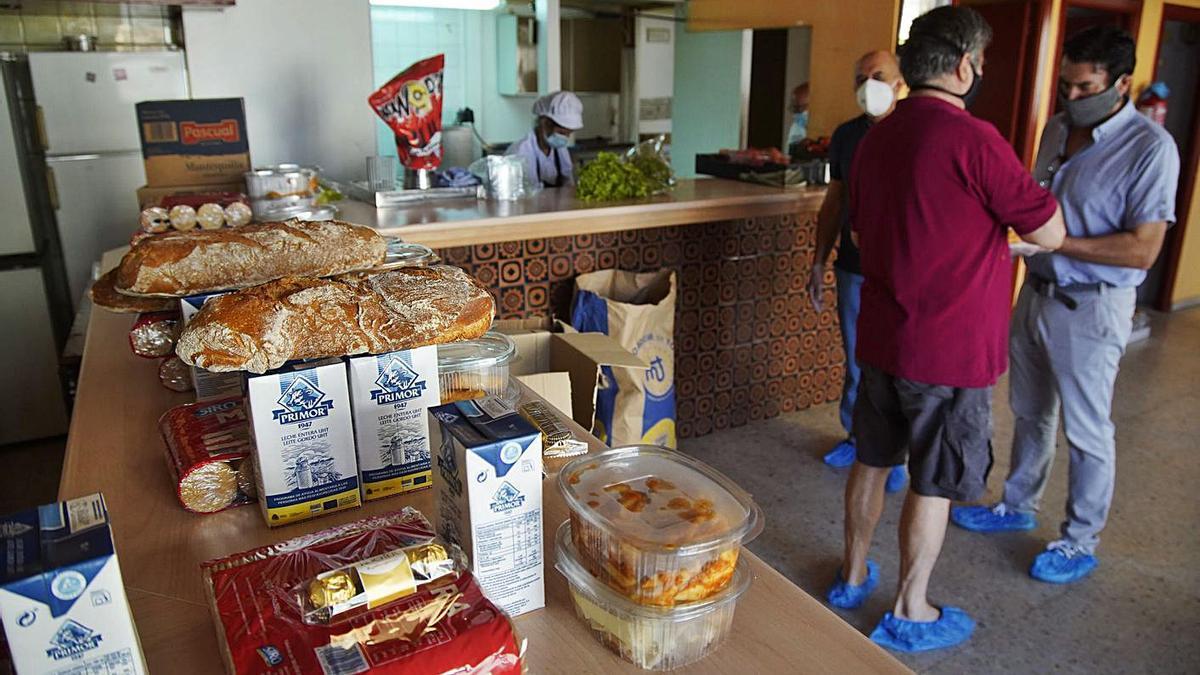 Voluntarios preparan lotes de alimentos para entregar en las casas. | Jose Luis Fernández