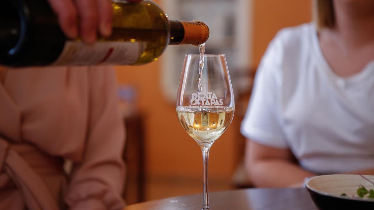 Un camarero sirve una copa de vino a dos clientes de una taberna.