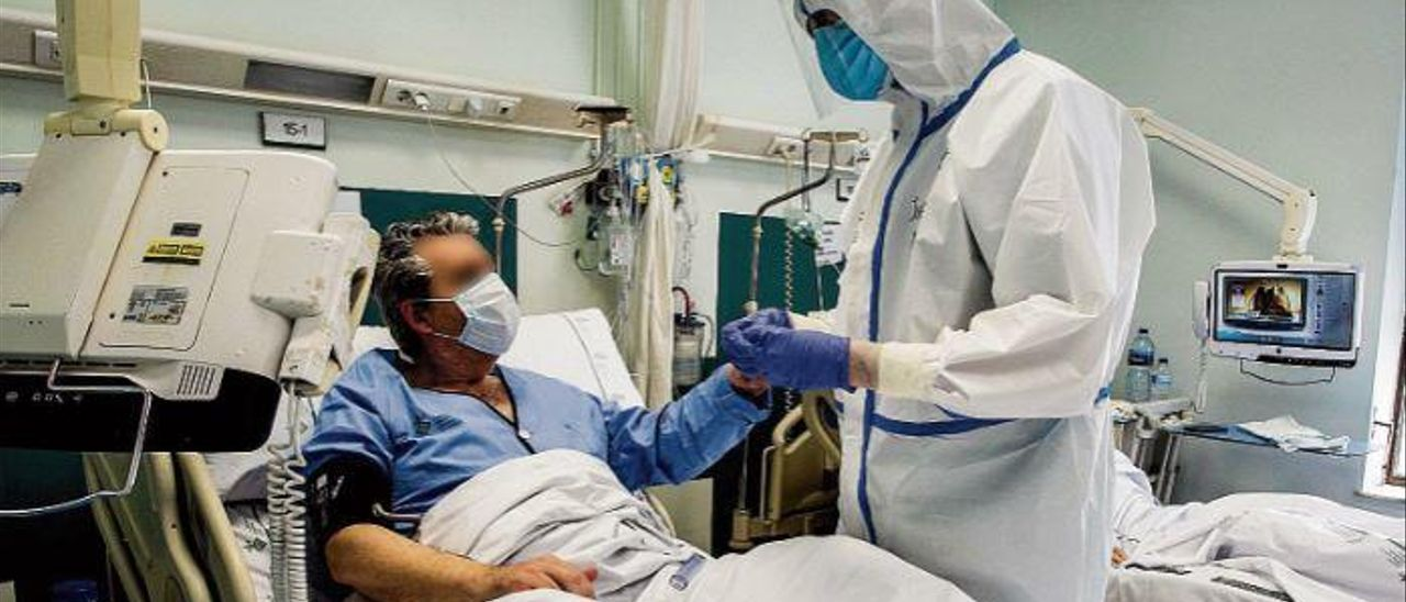 Un sanitario atendiendo a un enfermo covid-19 en el HOspital General de València.