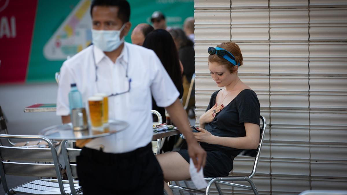 Un camarero sirve en la terraza de un bar