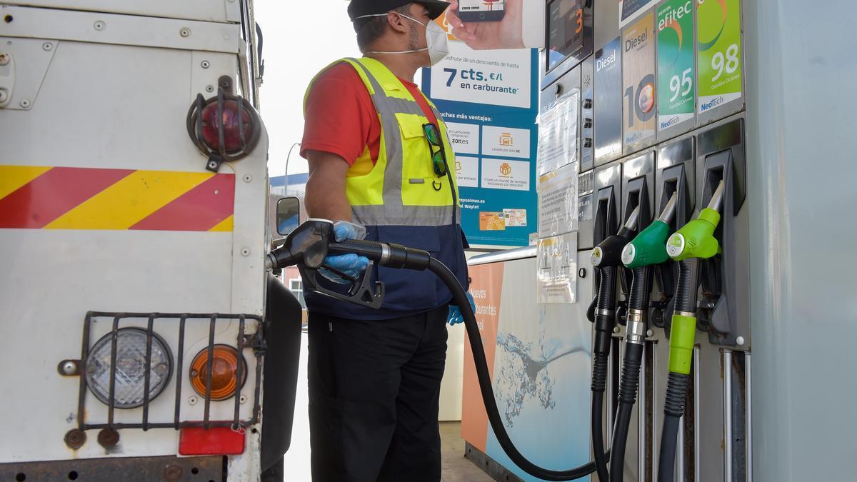 Un conductor reposta su vehículo en una gasolinera.