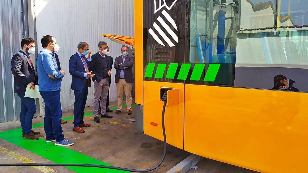 Guillermo Luján, Manuel Martínez, Jordi Sebastià y Arcadi España observan uno de los autobuses eléctricos de la concesionaria. | A.C.