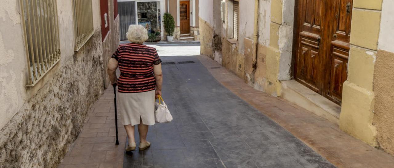 Una mujer paseando por las calles de Alcoleja, una población del interior de la provincia.