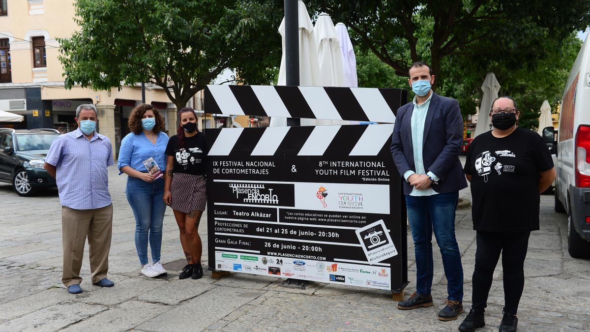Organizadores y colaboradores de los festivales, junto a la claqueta que anuncia la semana de cine.