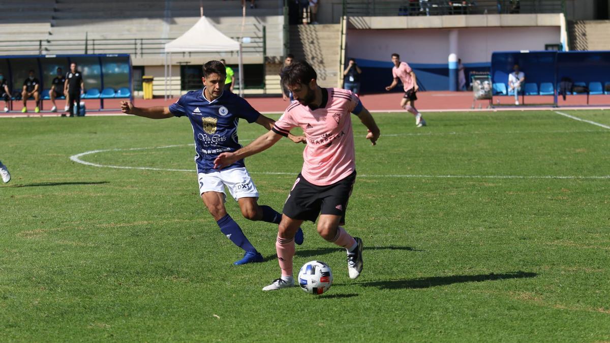Álex Bernal controla la pelota ante Pablo Santana