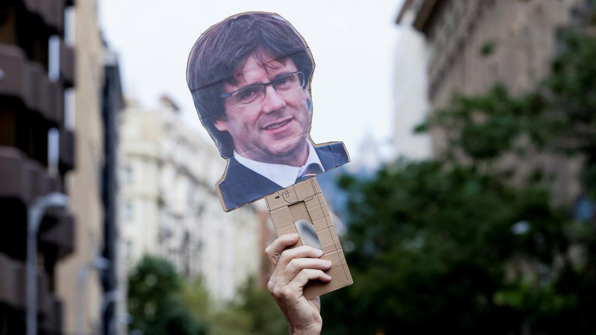 Un cartell amb una cara de Carles Puigdemont durant la manfiestació aquest divendres