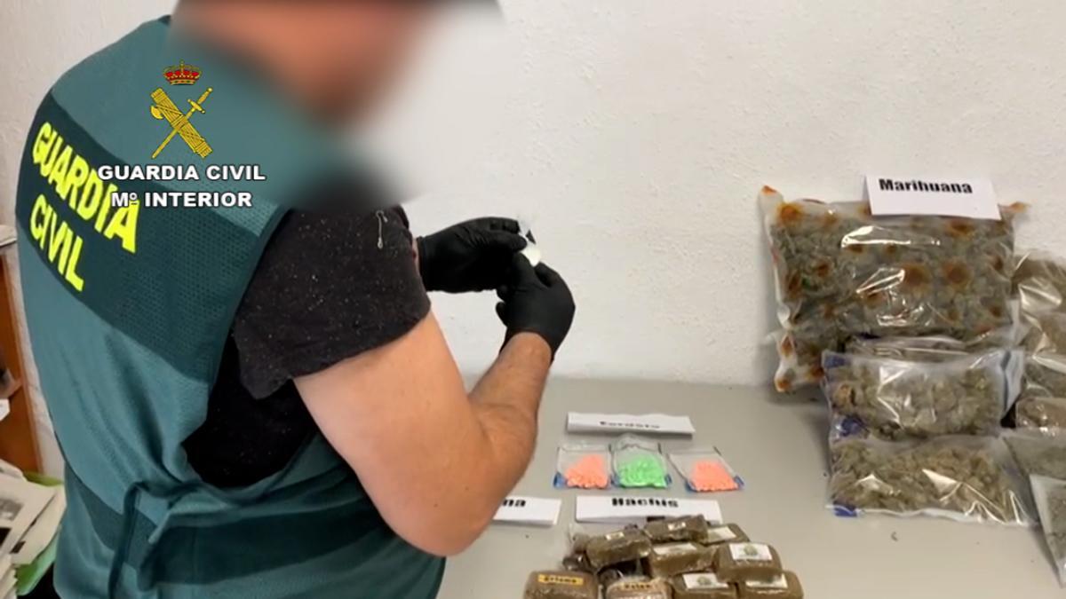 Un agente de la Guardia Civil con la droga intervenida en la operación-