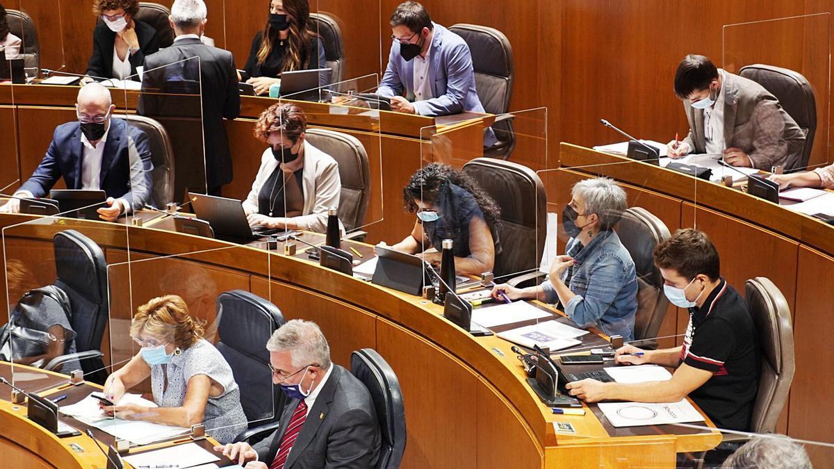Los consejeros Olona y Broto, en la primera fila, junto a las bancadas llenas de los parlamentarios de Podemos, PSOE e Izquierda Unida. | CORTES DE ARAGÓN
