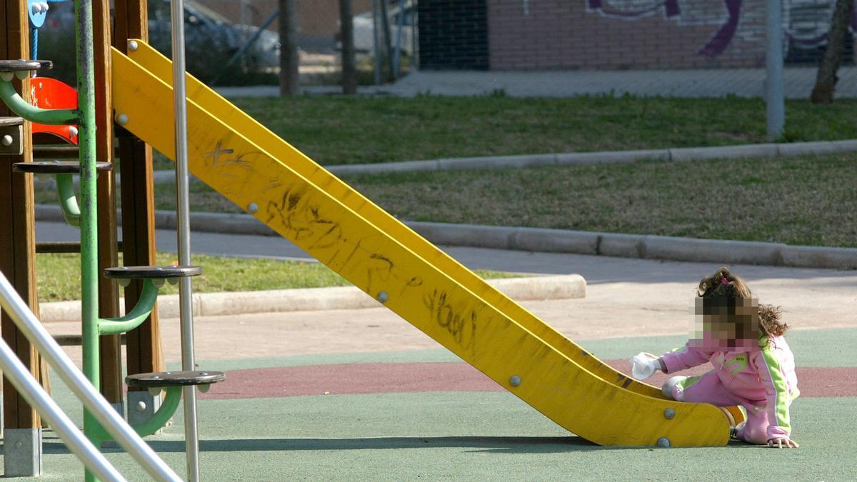 Una niña jugando sol en un parque, tras tirarse de un tobogán.