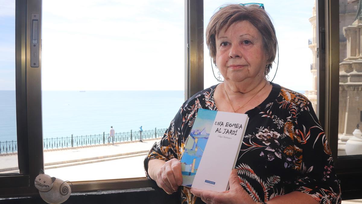 L'escriptora Olga Xirinacs subjectant la darrera obra publicada 'Una bomba en un jardí'