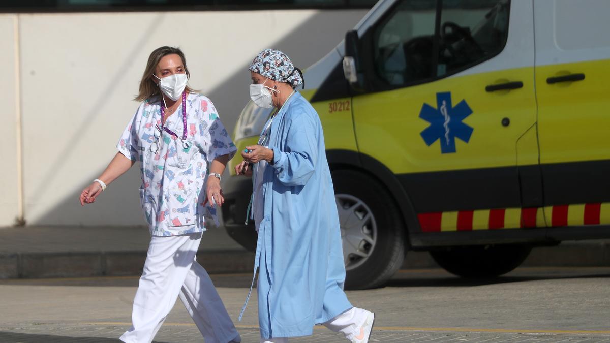 Dos trabajadoras sanitarias conversan en la entrada del Hospital La Fe de València durante la tercera ola.