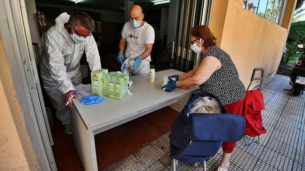 Trabajadores de una ONG entregan alimentos a una mujer durante el estado de alarma.