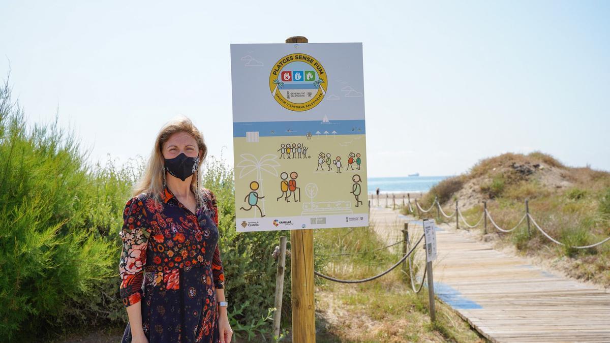 La alcaldesa de Castelló junto a un cartel recientemente instalado en la playa del Serradal.