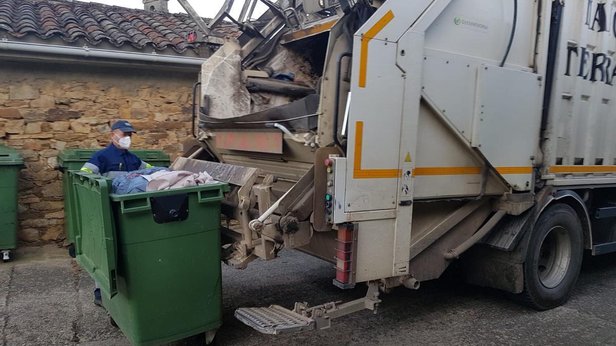 Un operario recogiendo la basura del contenedor con el camión