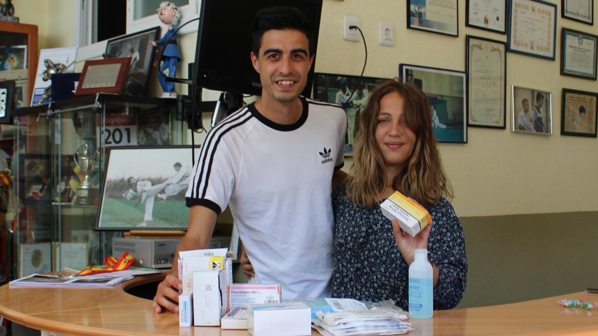 Joel González y Camila Lores con medicamentos recogidos en la recepción del gimnasio Tae-Sport.