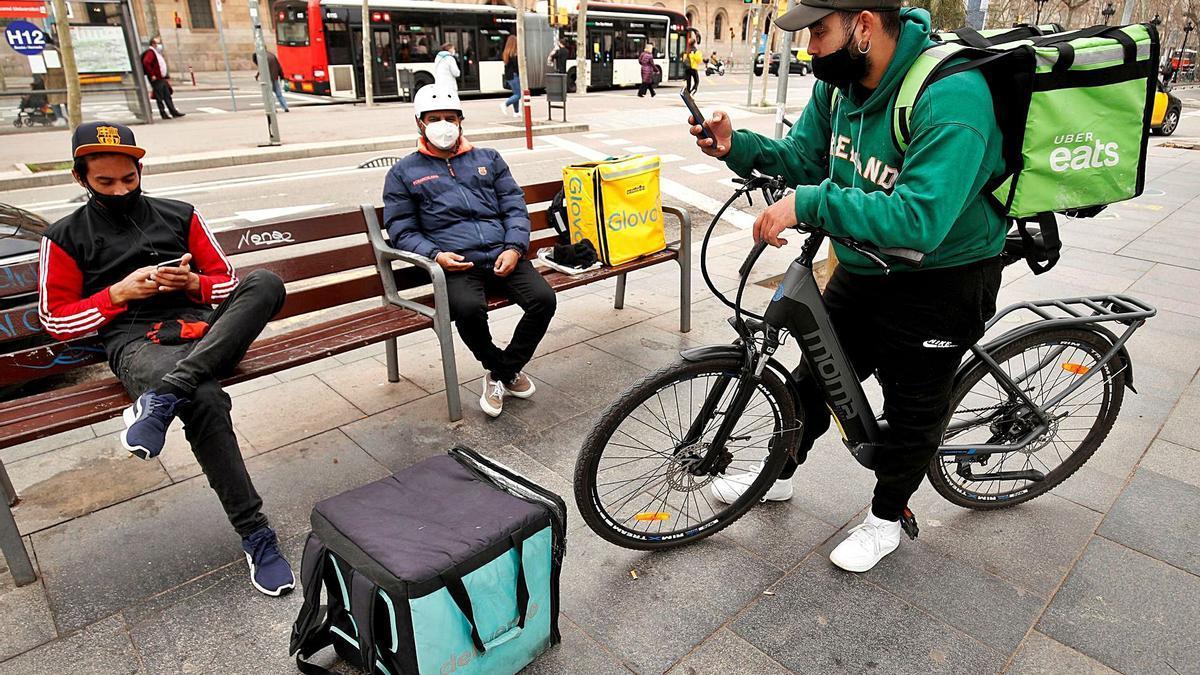 Tres 'riders' descansan mientras les llegan instrucciones de reparto. | | ALBERT GEA