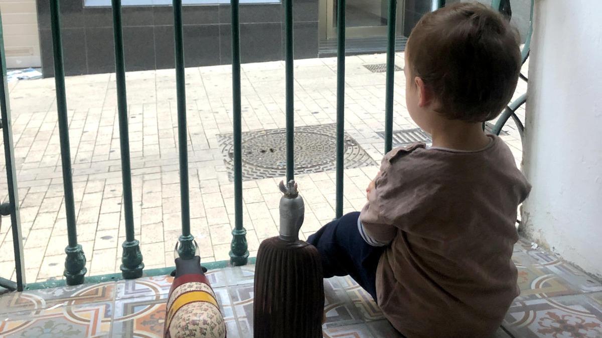 Un nen mira per la finestra de casa, durant el confinament.
