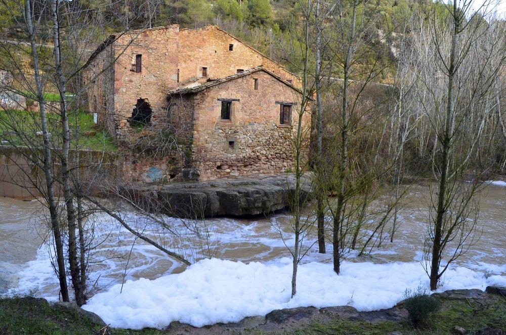 La riera de Marganell amb molta aigua i escuma blanca al davant de la Fassina de Castellbell