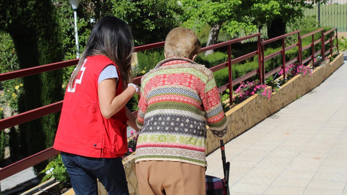 Una voluntaria de Cruz Roja acmopaña a una mujer mayor a vacunarse del covid en Montilla.