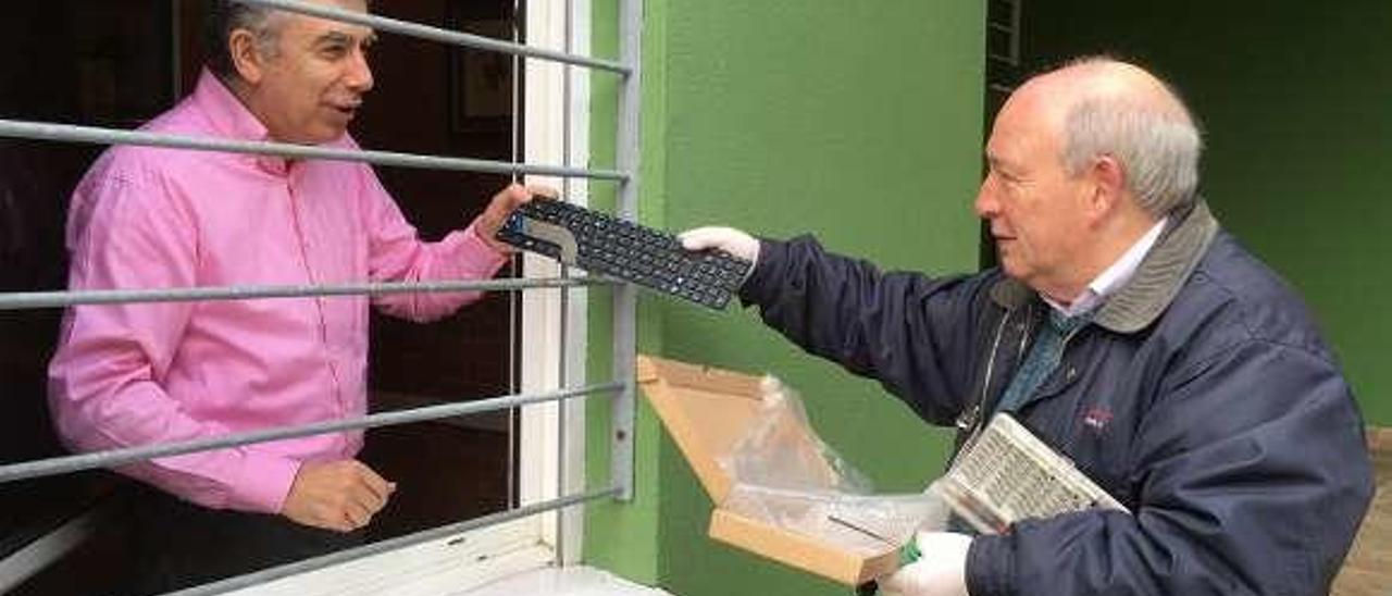 Luis Jesús Cocho entrega un ordenador a un cliente.