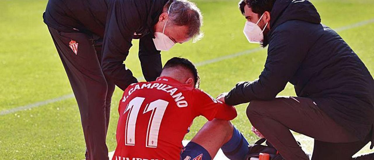 Miembros del cuerpo médico del Sporting atienden a Campuzano sobre el césped de El Molinón tras lesionarse en el derbi.