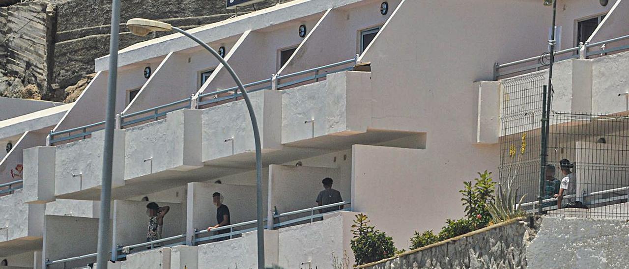 Varios menores se asoman desde sus habitaciones en los apartamentos Puerto Bello.     JOSÉ CARLOS GUERRA