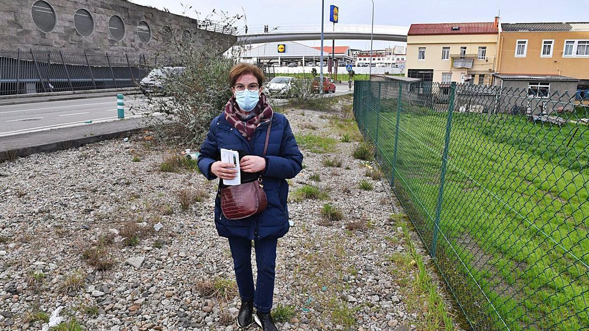 Yolanda Cedeira, en el terreno entre su finca y la acera que el Concello le obliga a comprar.     // VÍCTOR ECHAVE
