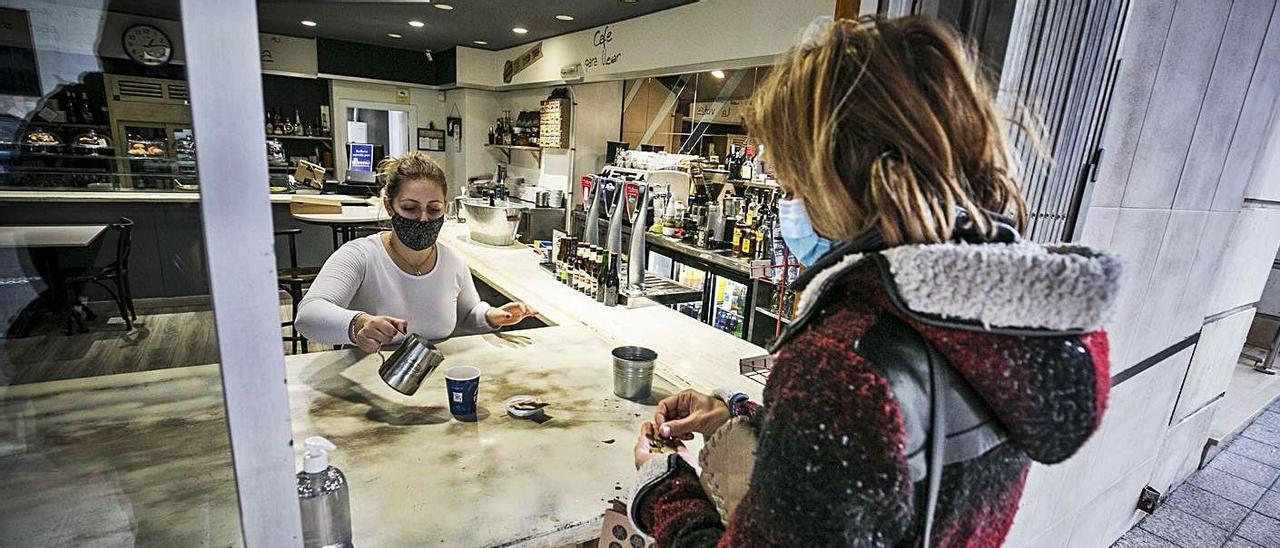 Vanesa García sirve a una clienta un café para llevar, en la calle Ventura Rodríguez de Oviedo. | Irma Collín