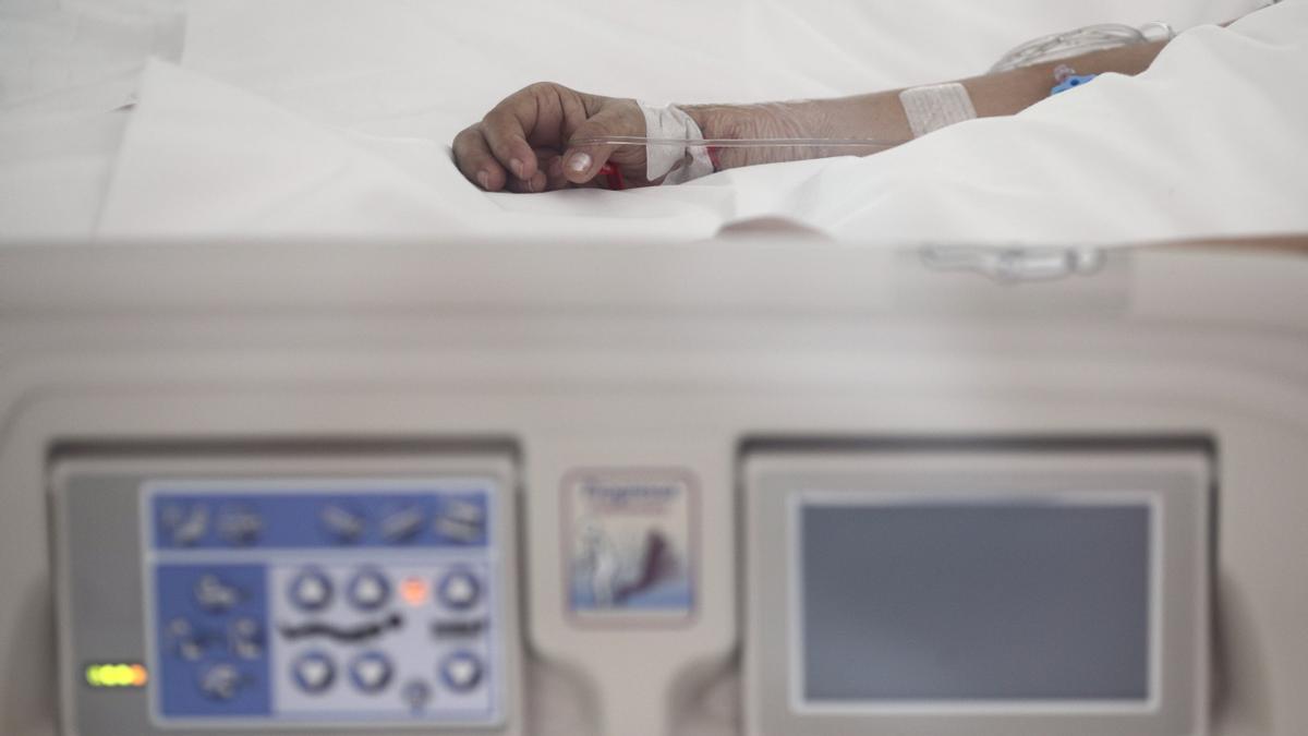 Archivo - Mano de un enfermo con vía subcutánea en una cama de la UCI del Hospital de Emergencias Isabel Zendal