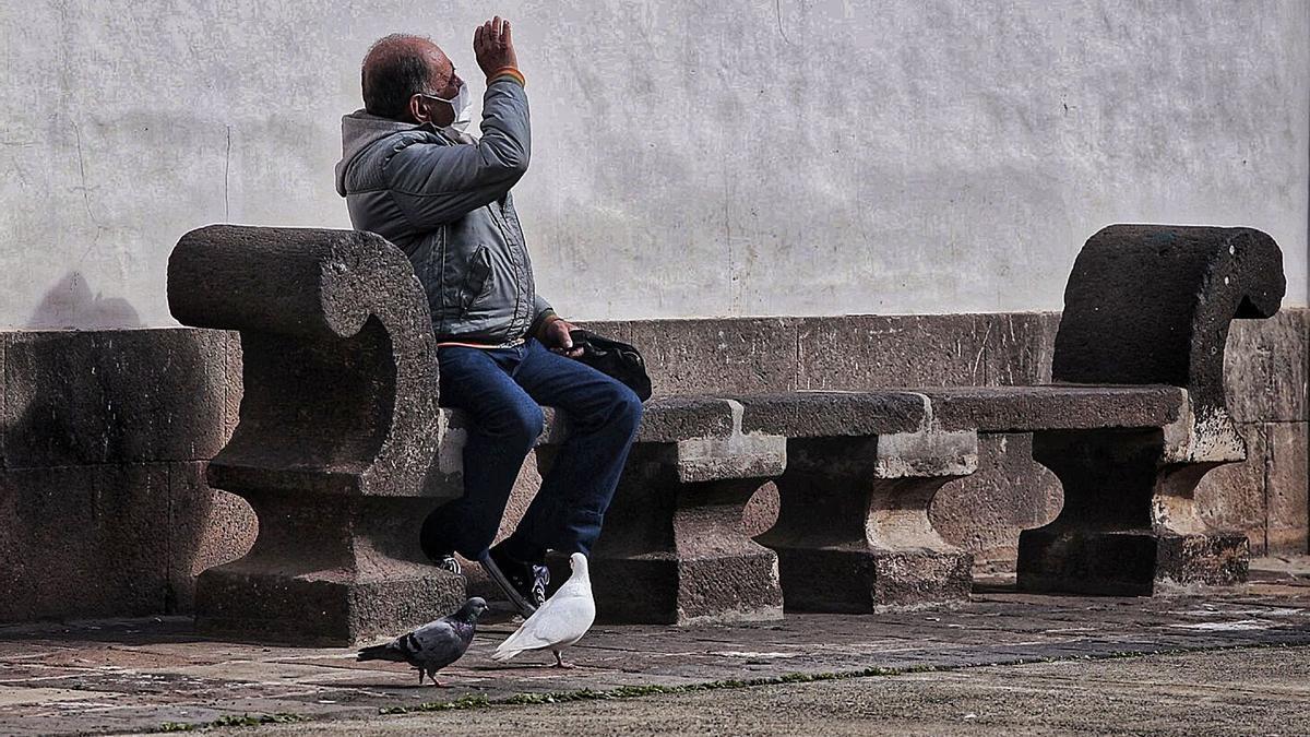 Un hombre cubre sus ojos para evitar los efectos del sol en una plaza ubicada en la Concepción de La Laguna.