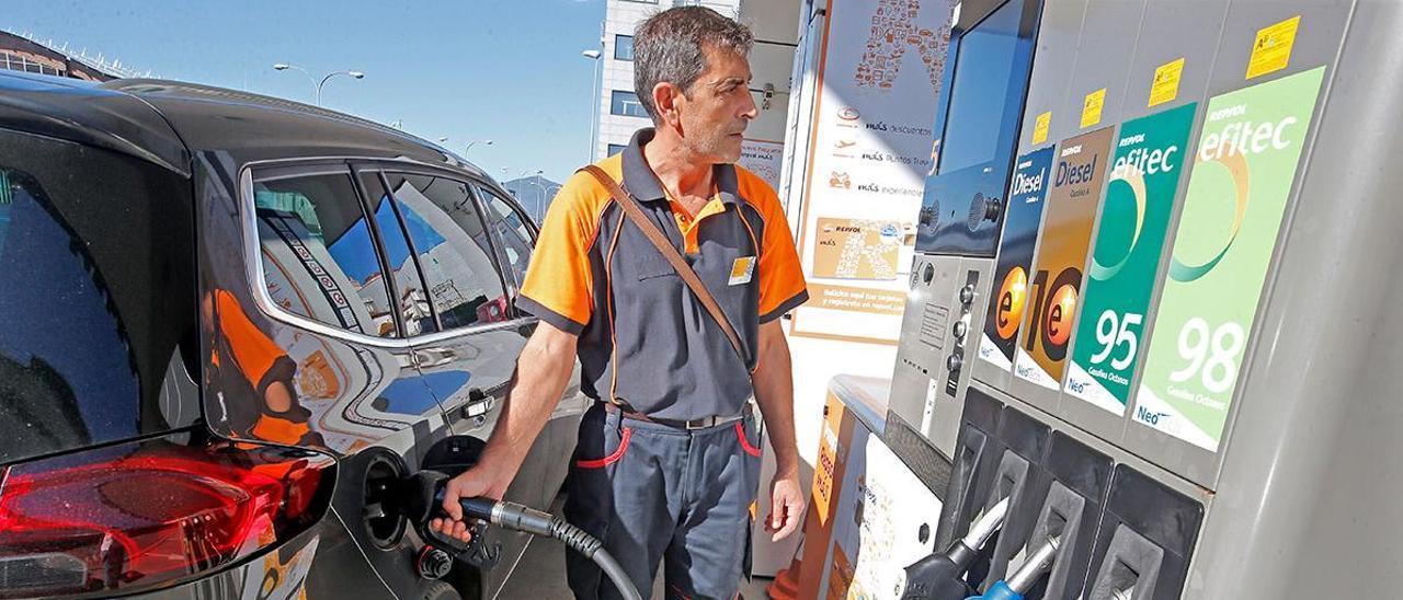 Empleado de una gasolinera llena el depósito a un cliente