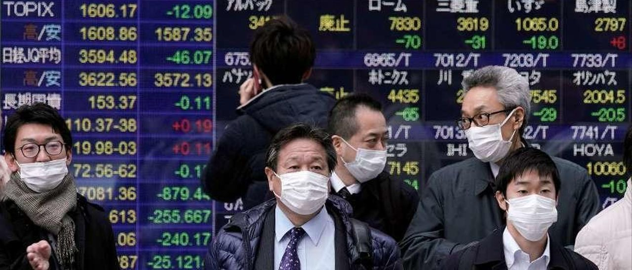 Ciudadanos de Tokio, ayer, delante de un panel con la evolución de las Bolsas. // Kimimasa Mayama