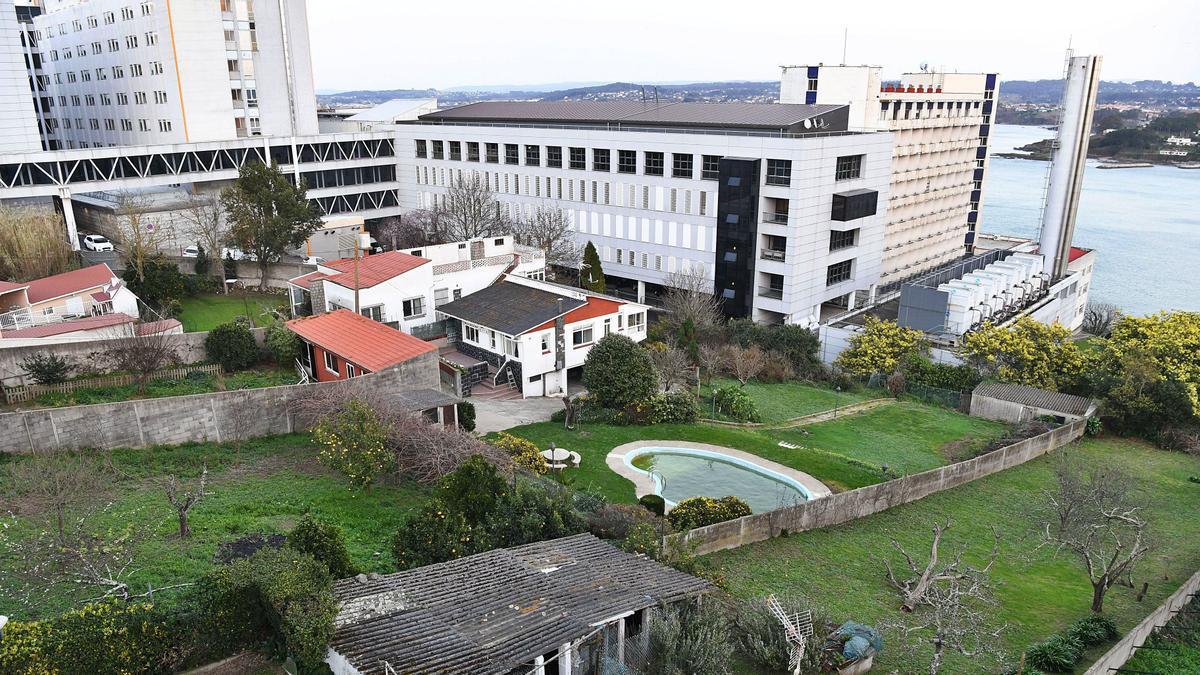 Viviendas afectadas por la ampliación del hospital, con las instalaciones actuales, al fondo.   | // CARLOS PARDELLAS