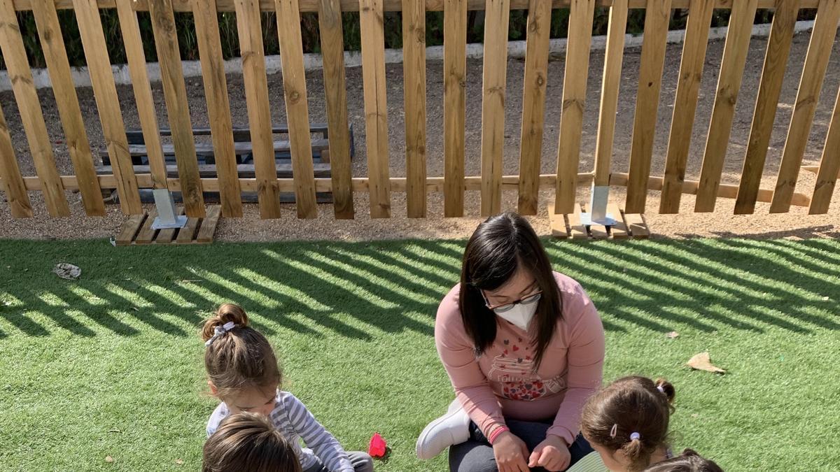 Una de las chicas de Down Mérida con los pequeños del centro infantil Los Bodegones.