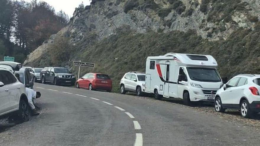 Vall d'en Bas: Cotxes aparcats a banda i banda de la GIV-5273, a la collada de Bracons