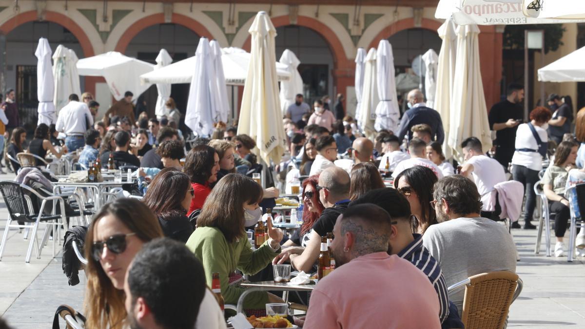 Clientes disfrutan de sus consumiciones en terrazas de bar.