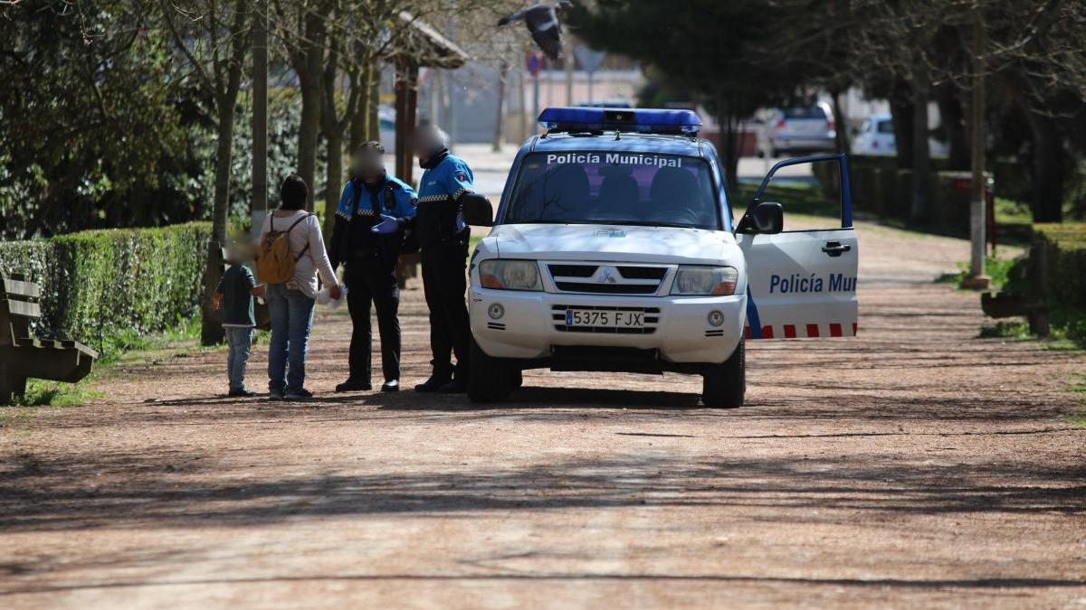 Agentes de la Policía Municipal llaman la atención a una familia durante los primeros días del confinamiento absoluto.