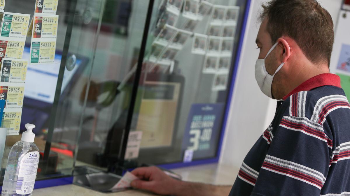 Un hombre compra lotería en una administración.