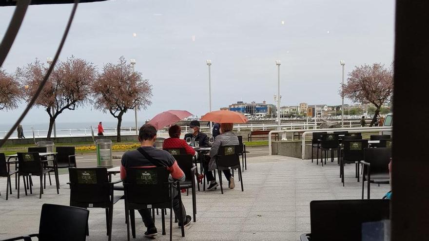 Terraceo con paraguas: los asturianos aprovechan al máximo la ampliación del horarios de los bares
