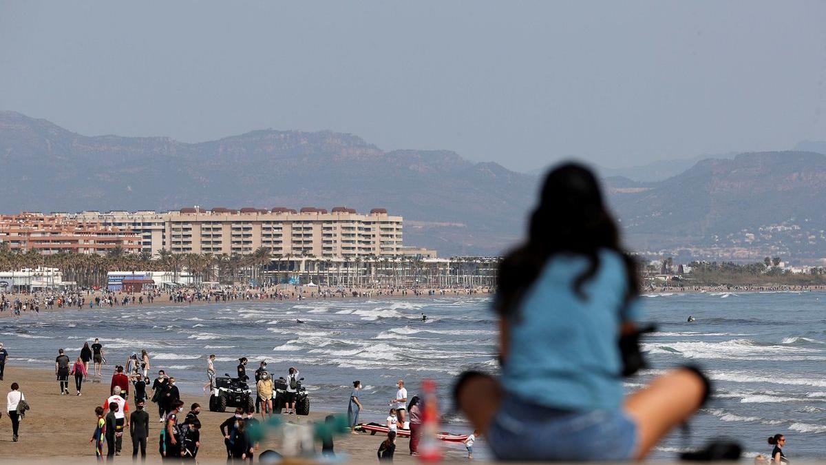 Una joven mira hacia la playa en el espigón de la Marina del Puerto de Valencia